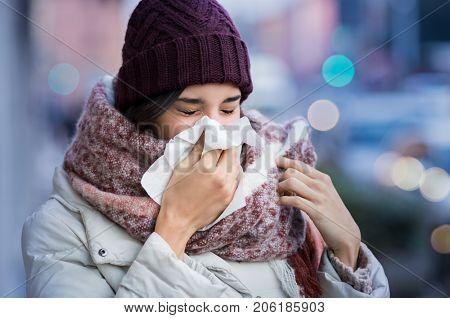 Pretty young woman blowing her nose with a tissue outdoor in winter. Young woman getting sick with f
