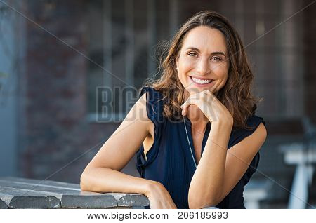 Portrait of beautiful mature woman sitting at coffee shop. Happy hispanic smiling woman sitting on a