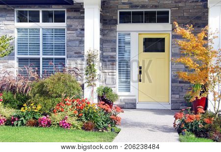 Pretty new home with a colorful front door and perennial garden.  stock photo