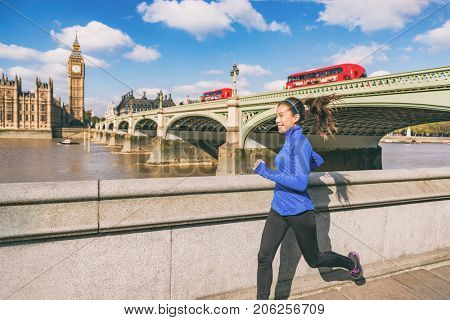 London runner woman running near Big Ben. Europe city Asian girl jogging training at Westminster bridge with red double decker bus. Fitness athlete happy in London, England, United Kingdom. stock photo