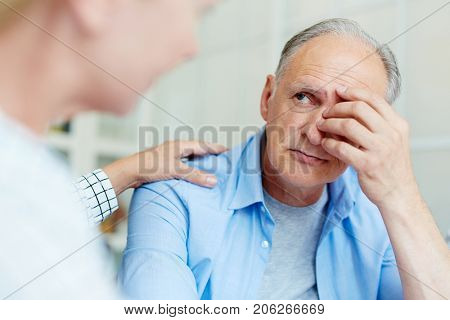 Worried senior man looking at his friend or wife reassuring him stock photo