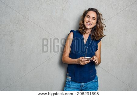 Smiling mature woman using smartphone and looking at camera. Happy woman typing on cellphone over gr