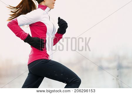 Winter running athlete woman on cold run jogging fast with speed and sprint on outside workout wearing warm clothing gloves, winter tights and wind jacket in snow weather. stock photo