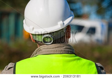 Rear view of construction worker on a building site and dressed in safety clothing of hard hat and high visibility vest stock photo