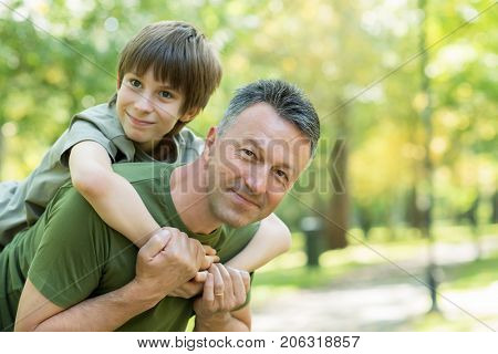 Portrait of father with his son having fun in autumn park. Piggyback. Family funny leisure. Happy boy playing with dad, fall nature outdoor stock photo