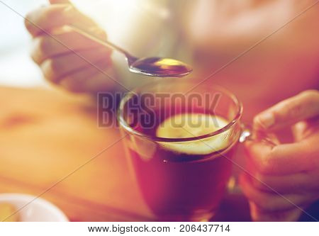 healthy food, eating and ethnoscience concept - close up of woman adding honey to tea cup with lemon stock photo