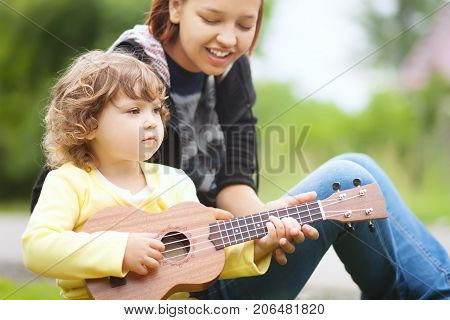 Young attractive nanny teachs little girl playing ukulele sunny day outdoors. Early music education. babysitting. elder sister. young mother stock photo