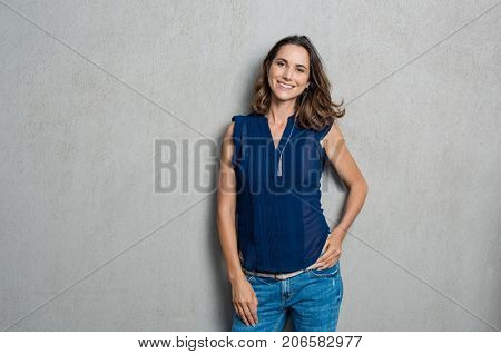 Portrait of cheerful mature woman standing against grey wall. Happy mid woman looking at camera agai