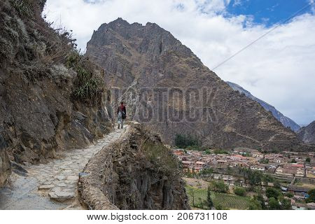 Tourist exploring the Inca Trails and the archaeological site at Ollantaytambo Sacred Valley travel destination in Cusco region Peru. Vacations and adventures in South America. stock photo