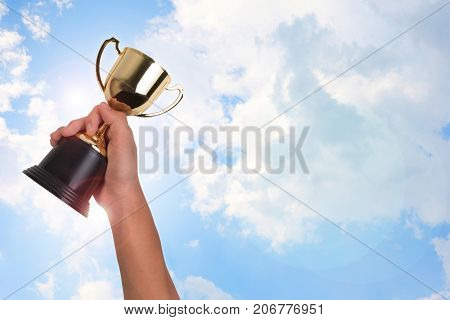Asian boy holding a gold trophy cup for first place champion award on blue sky. Boy holding up a gold trophy cup as a winner in school competition.