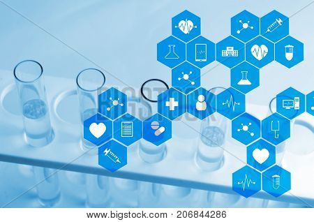close up chemical liquid in laboratory test tube with medical icon in hexagon pattern blue color tone laboratory science chemical and medical research concept soft and selective focus stock photo