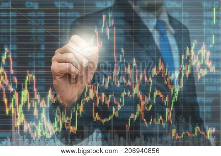 Businessman writing the trading graph of stock market on the virtual screen on photo blurred of citysscape building background Business stock market and trading concept, 3D illustration