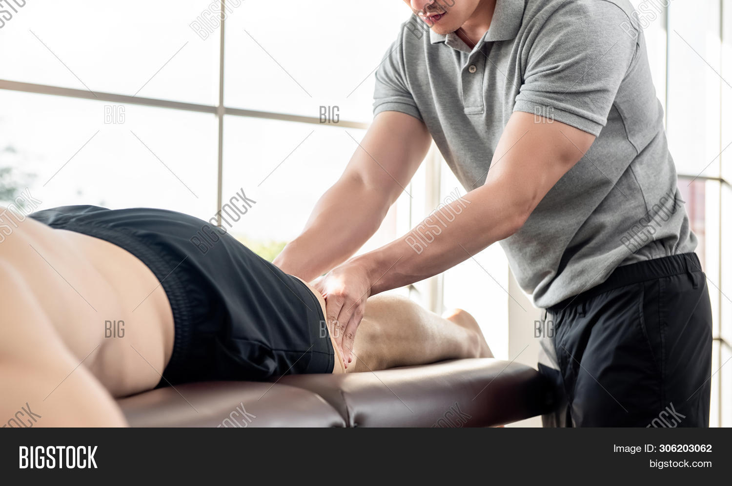 Male Therapist Giving Leg Massage To Athlete Patient On The Bed In Clinic, Sports Physical Therapy C