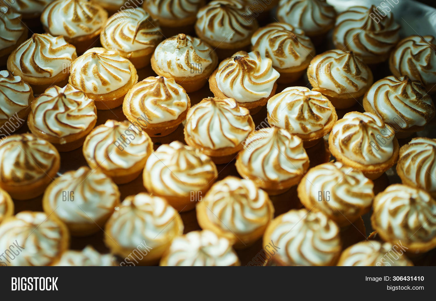 Sweet desserts and pastries on the table during the event. Catering servicing of guests and participants during mass events. Large number of sweet and cupcakes. Soft focus, bokeh, abstract.