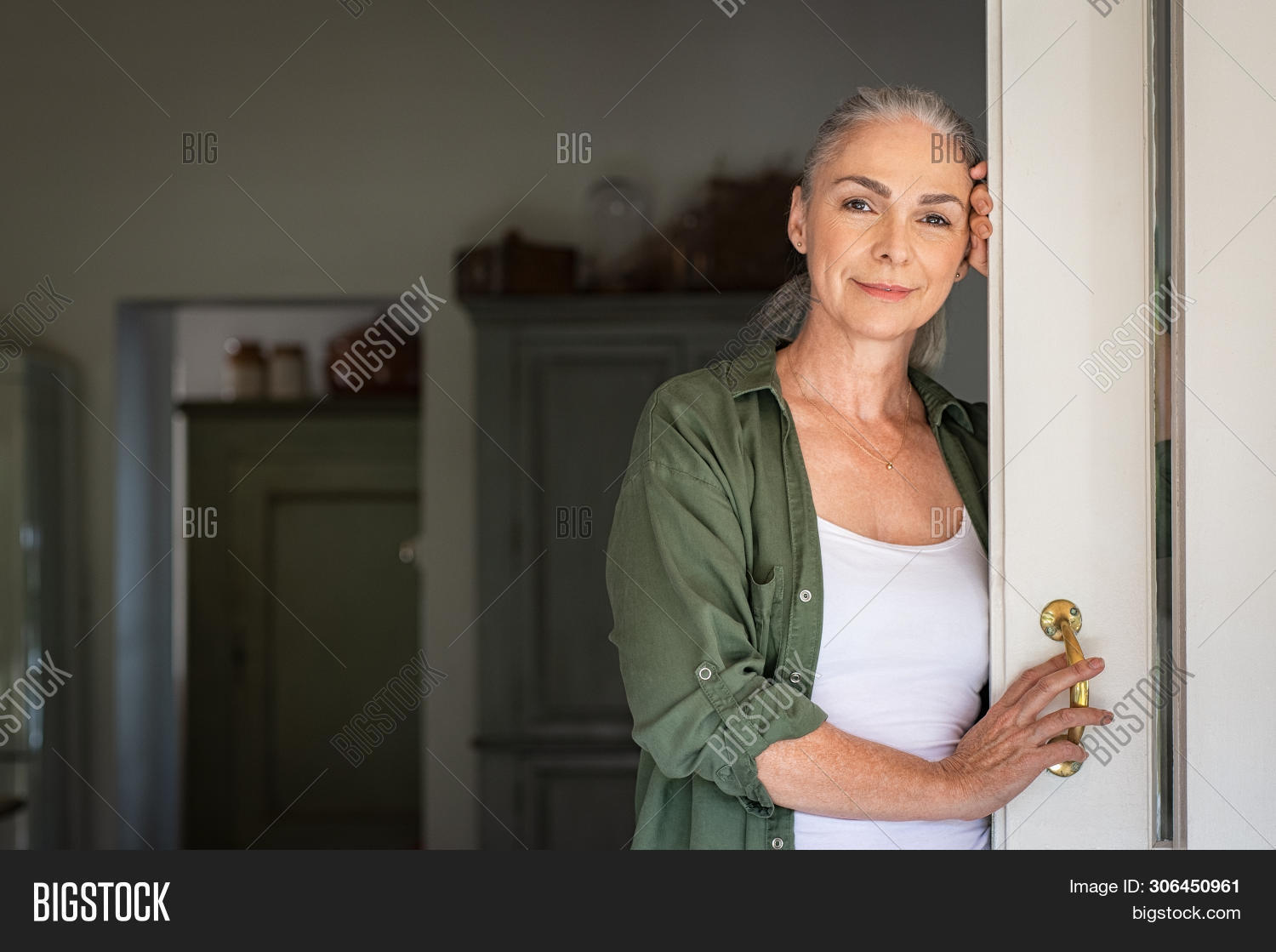 Portrait of senior woman leaning against door at home and looking at camera. Smiling mature woman st