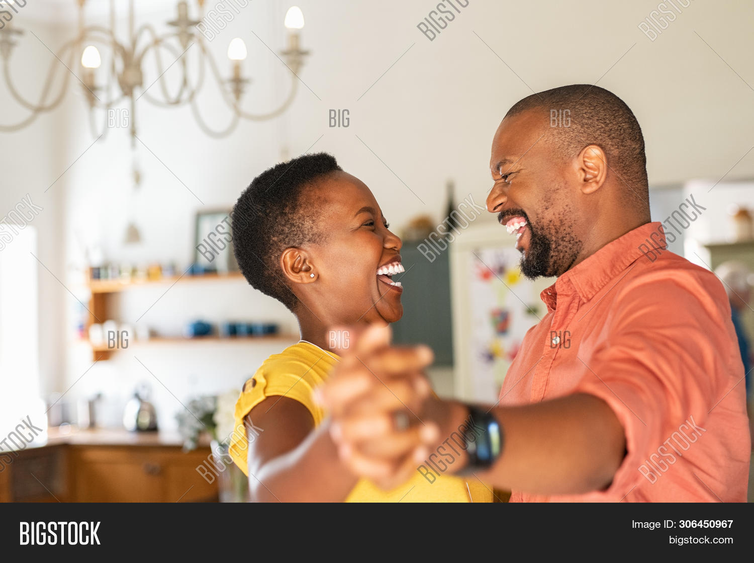 Cute mature couple dancing at home for their anniversary. Happy black woman enjoying a dance in the