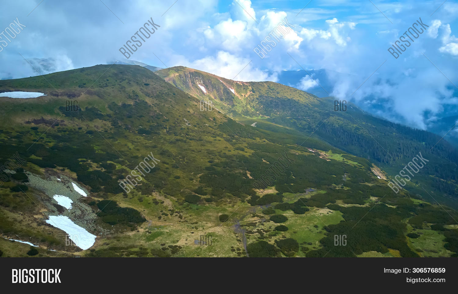 Mountain ridge with rocky outcrops. Panoramic view from the top of the ridge on background of valley. Carpathian Mountains