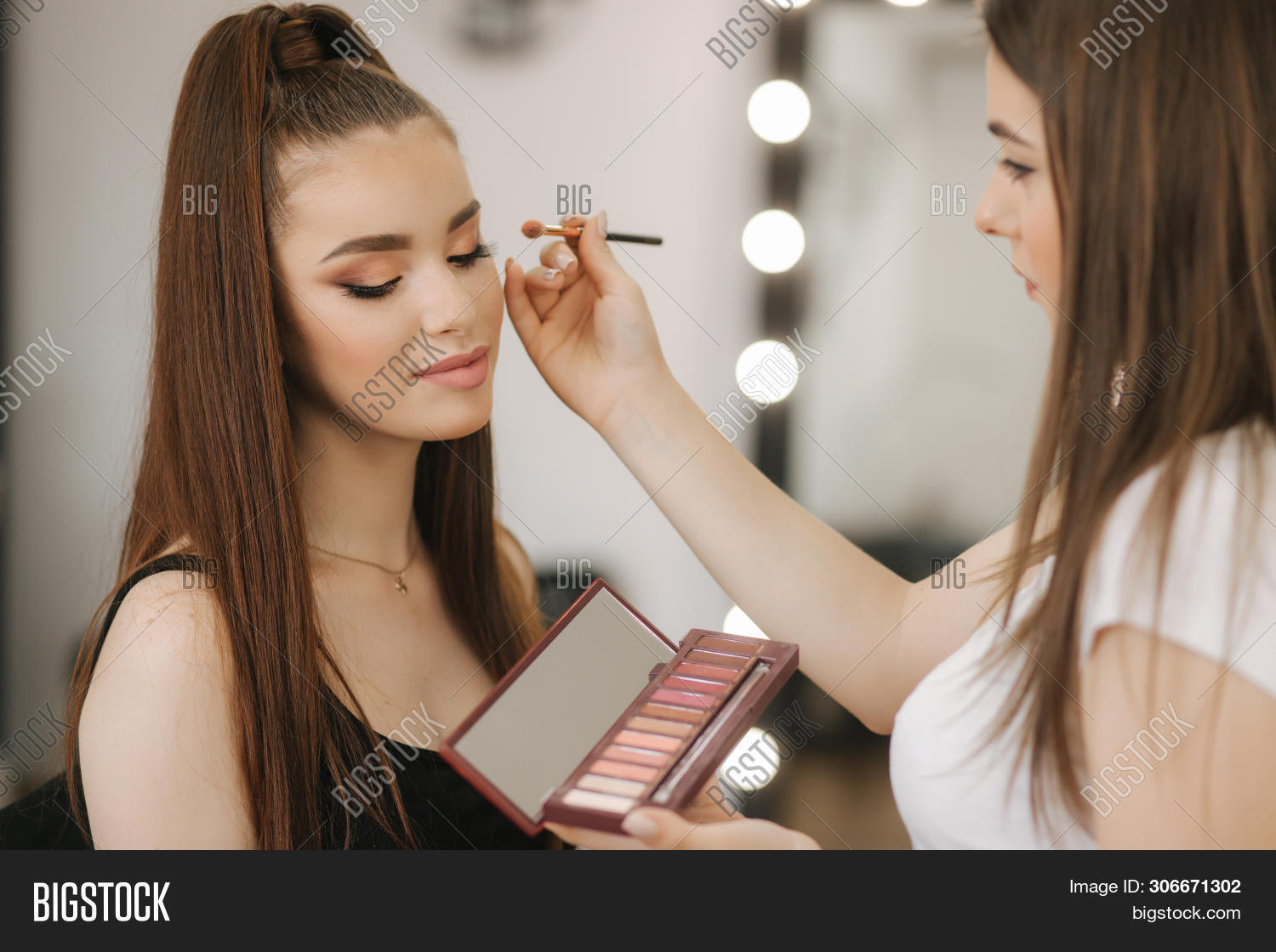 Makeup artist work in her beauty studio. Woman applying by professional make up master. Beautiful make up artist make a makeup for redhead model with freckles. She use a palette