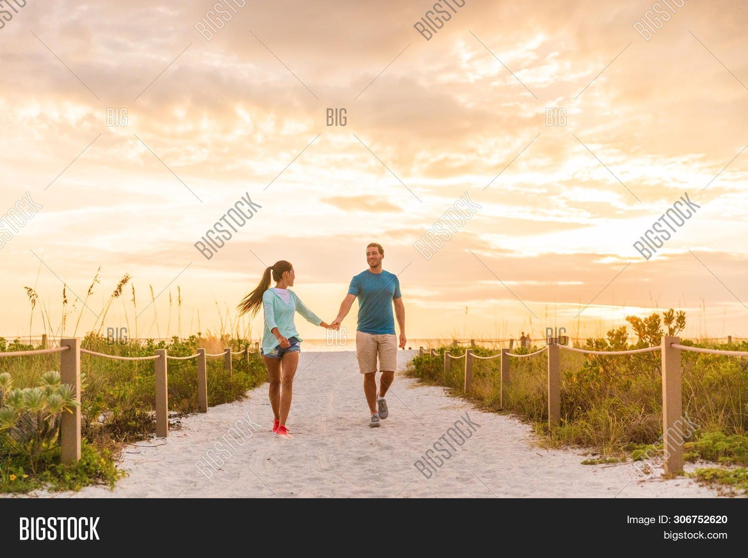 Happy young couple in love walking on romantic beach stroll at sunset. Lovers holding hands on Flori