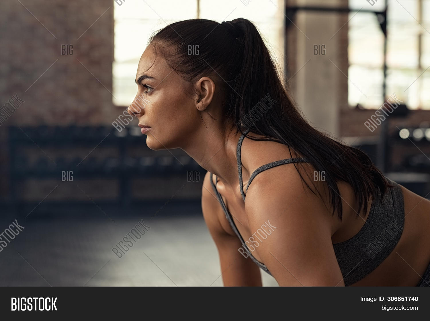 Young woman doing squat exercise while looking away at gym. Closeup of muscular girl while exercisin