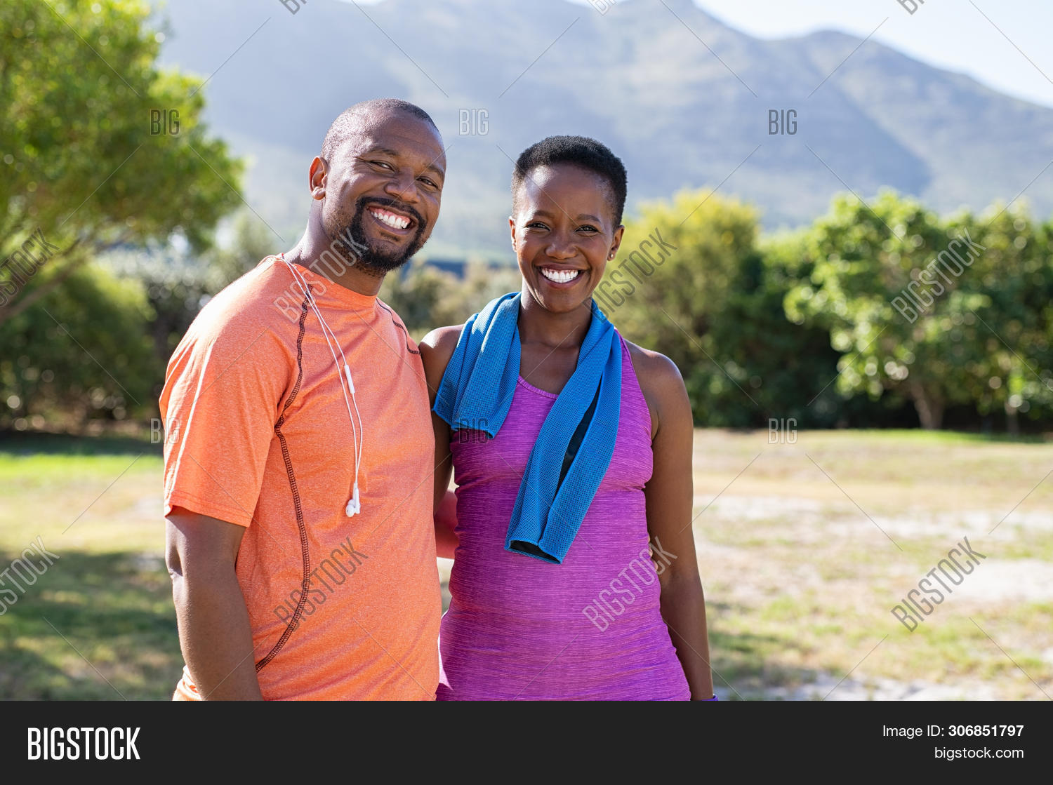 Portrait of black sporty couple looking at camera at park with copy space. Happy mature man and smil