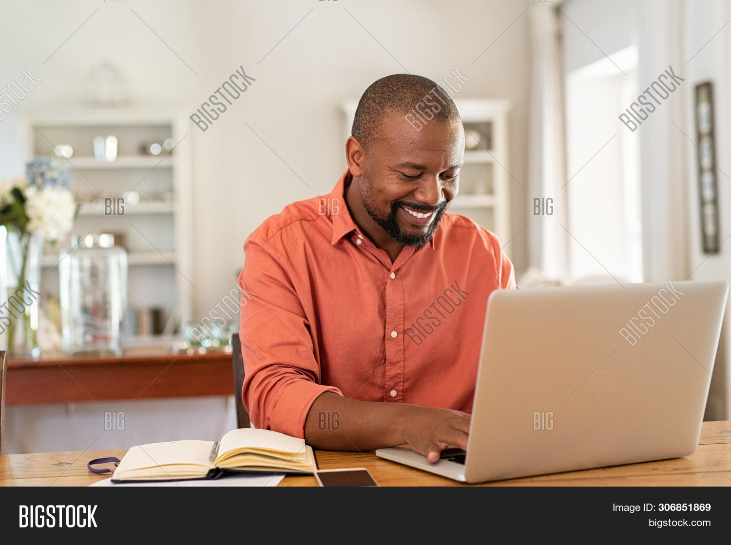Smiling black man using laptop at home in living room. Happy mature businessman send email and worki