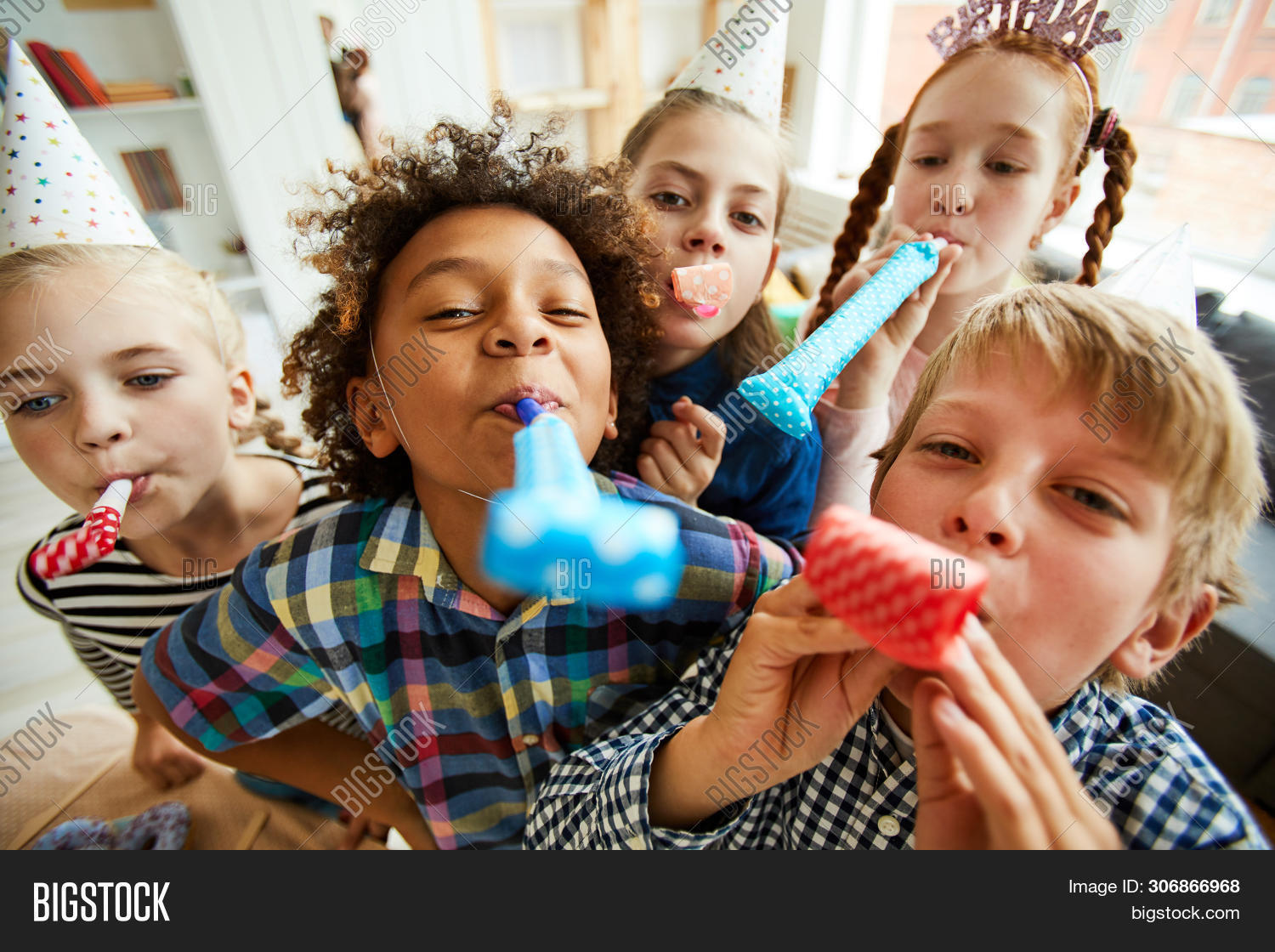 High Angle View At Multi Ethnic Group Of Children Blowing Party Horns At Camera