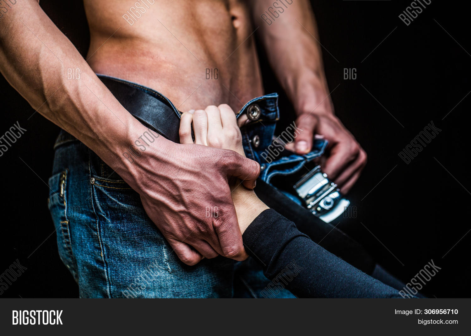 Brutal sex. Passionate young couple on dark background. Sensual touch. Sensual girl. Sexual abuse. Female hand unfolds mens zipper on jeans. Sexy woman roztebat man pants