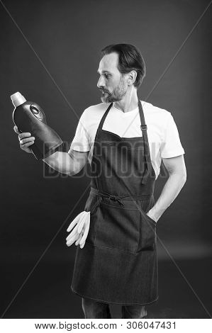 Household laundering. Senior man in apron ready for doing laundry. Mature man holding detergent bottle in hands. Eldery household worker wearing bib apron with rubber gloves. Keeping clothes spotless. stock photo
