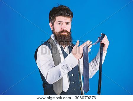 Bearded but elegant. Long bearded hipster choosing neckwear. Bearded man holding necktie. Cheerful man with unshaven bearded face and mustache hair with fashion accessories stock photo