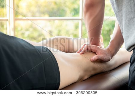 Male therapist giving leg and calf massage to athlete patient on the bed in clinic for sports physical therapy concept stock photo