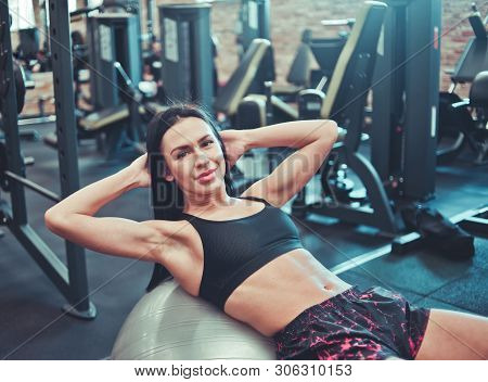 Abdominal muscle training. Purposeful fit brunette in sportswear doing twisting for abdominal muscles on fit ball in the gym stock photo