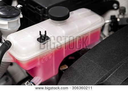 Close-up white expansion tank with pink antifreeze. Car coolant level in radiator system in car, automotive part. stock photo