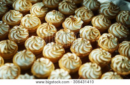 Sweet desserts and pastries on the table during the event. Catering servicing of guests and participants during mass events. Large number of sweet and cupcakes. Soft focus, bokeh, abstract. stock photo