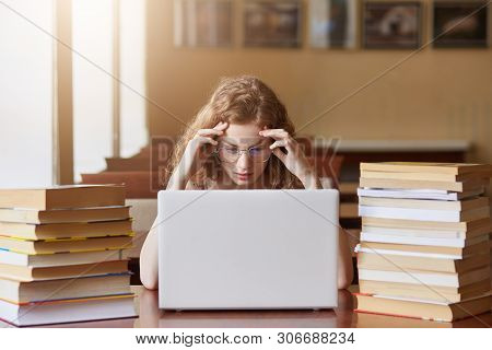 Portrait of stressed busy hard working student coping with all deadlines, being short of time, worried about her home assignments, touching her head with hands, being exhausted by doing tasks. stock photo