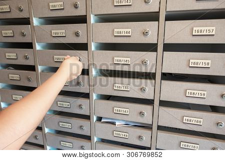 Close-Up of Woman Hand Insert a Key to Unlock Mailbox Locker in Apartment, Interior Mail Letterbox Cabinet in Condominium. Row of Post Locker in Residential Building. stock photo