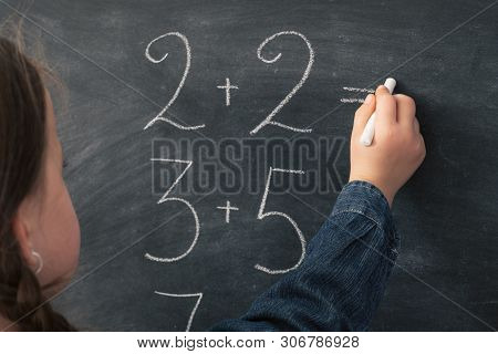 School Concept. Back View Of Young Girl Studying Mathematics, Doing Sum On Chalkboard.
