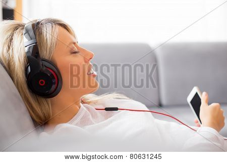 Relaxed woman listening to music on headphones at home stock photo