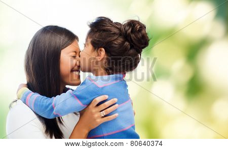 family, children and happy people concept - happy little girl hugging and kissing her mother over gr