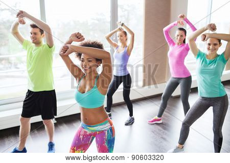 fitness, sport, dance and lifestyle concept - group of smiling people with coach dancing zumba in gy