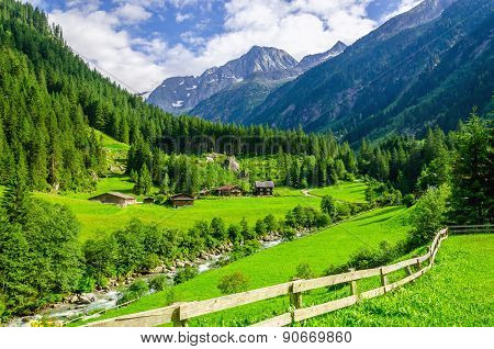 Green meadows, alpine cottages and mountain peaks