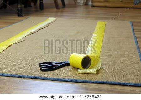 Anti-slip double sided adhesive texture tape with removable yellow plastic on one side. A roll of tape near scissors is placed on the floor rugs backing in two strips. stock photo