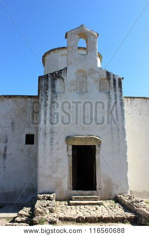 Ancient tiny small white church (smallest in Europe) against blue sky. Elegant little belfry located above the entrance with the open door. Small square window hole serves for air ventilation. Stone paved stairs lead to the entrance. stock photo