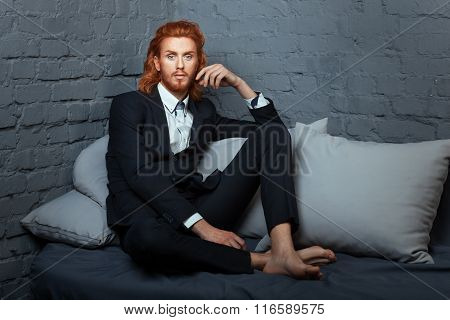 On the bed a man with freckles and red hair. He wore a stylish suit. stock photo