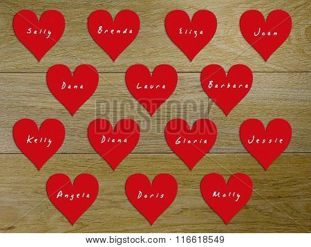 14 hearts with names of women on Valentine's Day. Background - a wooden board stock photo