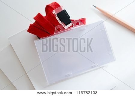 Blank ID or security card on office table, with red neck strap. stock photo