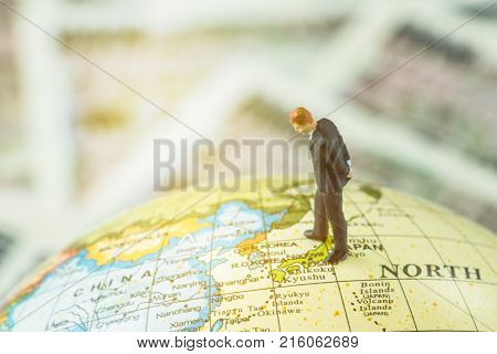 Miniature figure country leader man standing and looking at north korea map on globe as world critical nuclear missile war situation or war talk negotiation concept. stock photo