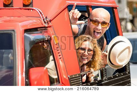 Happy couple of tourist travelers around Patong with tuk-tuk taxi car - Wander friends having fun on road trip in Phuket island Thailand - Travel concept with adult people on world tour - Warm filter stock photo