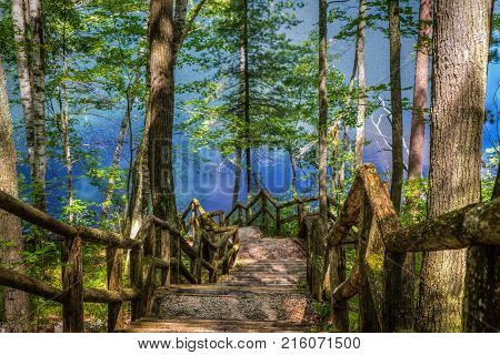 Stairs To The Lake. Wooden staircase winding downward to the aquamarine water of a remote Northern Michigan lake. stock photo