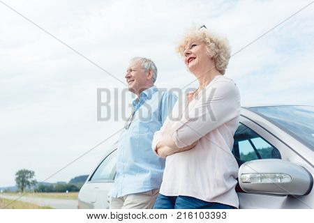 Low-angle view portrait of two senior people smiling and looking away with confidence and positive attitude while leaning on their car stock photo